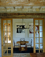 Double doors open onto the small dining room with paintings by British artist Ian McKeever