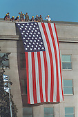 Firefighters unfurl a giant American flag over the scarred stone of the Pentagon, Wednesday,  September 12, 2001..Mandatory Credit: Paul Morse - White House via CNP.