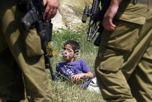 Israeli soldiers confront Palestinian child during a demonstration against Israel's separation barrier in the West Bank village of Nabi Saleh near Ramallah, Friday, June 29, 2012. Palestinians protest weekly against the neighbouring Jewish settlement of Halamish. Photo by Issam Rimawi