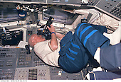 United States Senator John H. Glenn Jr. (Democrat of Ohio), payload specialist, focuses in on a target of opportunity as he participates in earth observations photography. The photo was taken with an electronic still camera (ESC) at 02:21:14 GMT, October 31, 1998..Credit: NASA via CNP