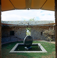A smooth stone sculptural fountain is situated in the centre of the inner courtyard of this contemporary house in New Mexico