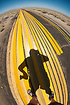 Yellow painted barrier striping used to test highway spray rig or to practice on abandoned paved roadway..Follow the yellow brick road...my shadow on the lines