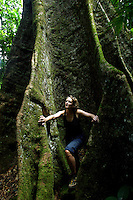 A tourist explores the giant roots of a Girandera Caribense tree.