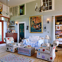 The clapboard interior wall separates the bedrooms from the main living area and is adorned with one of owner Edie Vonnegut's paintings