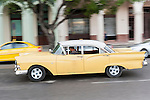 Havana, Cuba; a classic yellow and white 1957 Ford driving down the Paseo de Marti