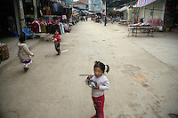 A young girl eats rice with chopsticks outside a market in Xinjie, Yunnan Province, China.