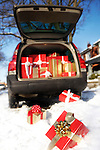 Christmas gifts falling on snow from an open trunk of a car
