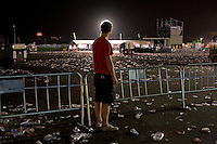 BENIC&Agrave;SSIM, SPAIN - A festival goer looks on as garbage trucks hoover up thousands of plastic cups and bottles discarded by the main stage of the festival site. ..Described by some as a Mediterranean Glastonbury, the Festival Internacional de Benic&agrave;ssim (FIB) is the largest music festival outside the UK to target British visitors. In 2010, seven of the eight main headline slots were filled by English bands...A small coastal town of 13,000 inhabitants, Benic&agrave;ssim hosted some 200,000 visitors in 2009, with 40% of those believed to be coming from the UK. In 2010, attendances fell to 127,000 visitors but the percentage of UK visitors is believed to have risen.
