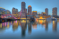 Buildings of the skyline are illuminated and reflected off the waters of the harbor as twilight descends on Boston, Massachusetts.