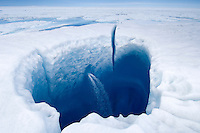 Cracks and holes cover the melting Greenland ice sheet surface in summer.