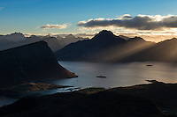 Rays of light shine over mountains and Nappstraumen from summit of Holandsmelen mountain peak, Vestvagoy, Lofoten Islands, Norway