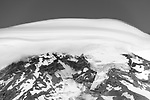 "Tight shot of the top of Mt. Rainier, under a lenticular ""cap"" cloud. You can see one of the glaciers clearly ... the thickest glacier on the mountain is 700 feet thick. http://www.gorp.com/parks-guide/travel-ta-mount-rainier-national-park-glaciers-sidwcmdev_067752.html Lenticular ""cap"" cloud over Mt. Rainier"