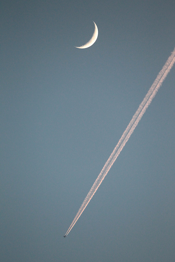 A plane flies past a crescent moon in the early evening sky on the East coast of the United States. Photo/Andrew Shurtleff