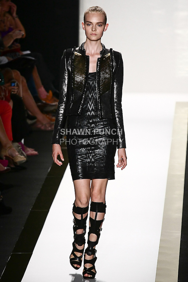 Nimue Smit walks the runway in a black foil bandage dress, black/metallic suede novelty jacket, and black gladiator boot, by Max Azria for the Herve Leger by Max Azria Spring 2012 fashion show, during Mercedes-Benz Fashion Week Spring 2012.