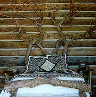 In the master bedroom of this Adirondack-inspired lodge in Aspen the bed has been created from fallen branches found on the property