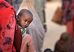 A newly arrived Somali child surveys the world from its mother's back while waiting with her family to be processed in the reception center of the Dagahaley refugee camp, part of the Dadaab refugee complex in northeastern Kenya.
