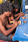 Maabaidhoo Island, Laamu Atoll, Maldives; the crew of the M/Y Conte Max live aboard dive boat making jewelry out of sea shells and coconut husks
