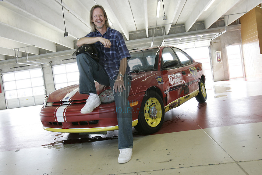"Brooks Everett, pastor of the Community Bible Church in Stockbridge, poses with a car at Atlanta Motor Speedway in Hampton, Ga. on Tuesday, July 9, 2007. Everett won the ""Faster Pastor"" race last year at the Speedway and will try again for first place this year."
