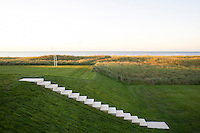 Indiana limestone steps lead down to a lawn behind the dunes, their tuffty grasses glowing gold in the evening sun