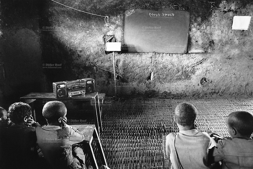 Ethiopia. West Gujam. Danbecha district. Anjeni is a small village. A group of pupils sit at school and listen to a recorded radio program while their teacher is absent. The walls of the classroom are made of mud. © 1996 Didier Ruef