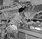 """Bethel Park PA:  View of a woman selecting produce at Bethel Market Grocery Store.  Marjorie Stewart is shopping for produce during an onsite photography assignment for Bethel Market.  Bethel Market was """"the"""" grocery store in Bethel Park from the late 1950s through the early 1980s."""