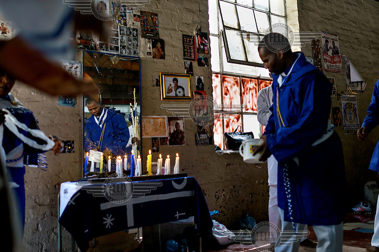 Members of the Zionist Church hold a service in the weight's room of George Khosi's Hillbrow Boxing Club. The church rents the space for a Sunday 'spirited prayer meeting'.  Hillbrow, in downtown Johannesburg, is the city's most notorious neighbourhood. It is overcrowded, ridden with illegal squats and suffers from high levels of crime much of which is related to the thriving illicit drug trade. Against this backdrop, George Khosi's story is not atypical. A childhood spent on the streets, where he survived by committing petty crime and hustling, led to imprisonment at the age of 16. Because he was big and looked older than his age this incarceration was in an adult institution. Here he began to fight since, as he says 'they wanted to make me a woman and I didn't want to be a woman.' When he got out, he took up boxing in earnest.His prospects as a professional boxer looked bright until he was shot and left for dead during a burglary. He lost his right eye and now walks with a limp. His boxing career seemed over but George picked up his gloves again, this time to teach Hillbrow's youngsters. His gym became a place of hope and discipline for local youth, keeping them of the streets and even producing some national champions.