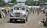 A vehicle from a United Nations peacekeeping contingent drives through a camp in rebel-held territory in the eastern Congo. Families displaced by fighting between rebel Tutsi General Laurent Nkunda and the Congolese military took refuge in this camp they established in the shadow of the UN base in the village of Kiwanja. According to aid workers and human rights groups, rebel soldiers executed some 150 people here in a 24-hour period in early November. The killings took place half a mile from the UN base, yet the 120 UN peacekeepers, part of the largest UN peacekeeping contingent in the world, did not take any action to stop the violence. ..