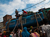 Local slum dwellers gather to collect water from a water tank outside their slum in Govind Puri, New Delhi, India.