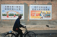 China. Province of Henan. Village Xiaotan. An old man with gray hair rides his bicycle and passes in front of two large posters. The one on the left is a recommendation of the chinese government policy for the one child per family. The second on the right is the strength of chinese science on future developments in towns, education and space-rocket. © 2004 Didier Ruef