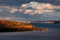 The clouds rolling back to reveal the fall colors of Grand Island, Pictured Rocks in the background.<br />