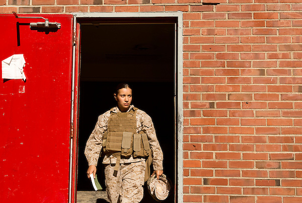 October 23, 2014. Camp LeJeune, North Carolina.<br />  Cpl. Raquel Mathieu heads out of the door of the Indoor Simulated Marksmanship Trainer. The ISMT allows Marines to train on different weapons in various simulated combat scenarios before taking part in live fire exercises.<br />  The Ground Combat Element Integrated Task Force is a battalion level unit created in an effort to assess Marines in a series of physical and medical tests to establish baseline standards as the Corps analyze the best way to possibly integrate female Marines into combat arms occupational specialities, such as infantry personnel, for which they were previously not eligible. The unit will be comprised of approx. 650 Marines in total, with about 400 of those being volunteers, both male and female. <br />  Jeremy M. Lange for the Wall Street Journal<br /> COED