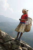 A young girl carries a traditional Nepali basket called a Doko. Through the trails of the Middle Hills, a new generation of Nepali children is being introduced to strangers from around the world who trek through their towns and villages.