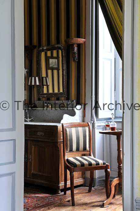 The bathroom leads off one of the master bedrooms and is decorated in an elegant combination of masculine stripes