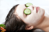Young woman getting a facial treatment with cucumbers on her eyes at a spa. **model release available**