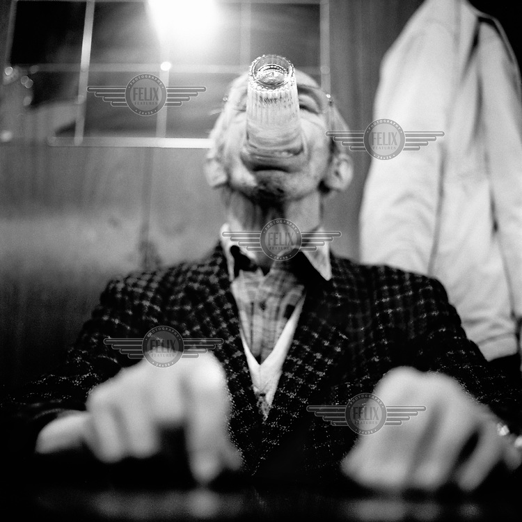 A man holding a glass in his mouth in a bar.