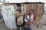 A family in the Haitian village of Dabonne stands in front of the temporary shelter they built following the destruction of their home in a January 12 earthquake. They used old lumber salvaged from the ruins of their previous house.