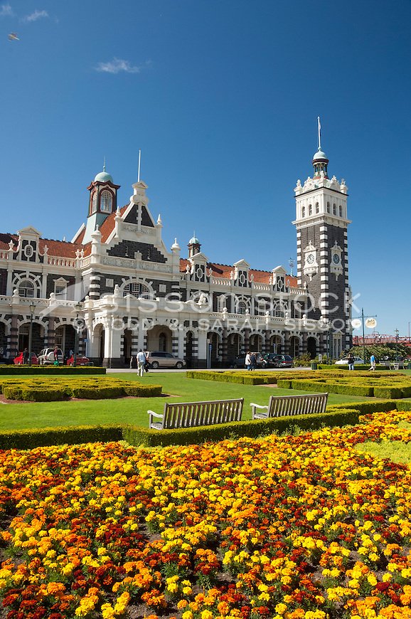 Bright orange and yellow flowers in gardens in front of the historic Dunedin Railway station building on a blue sky day,  Otago, South Island, New Zealand- stock photo, canvas, fine art print