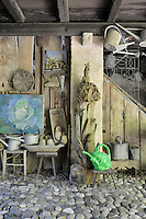 A rustic garden room with a wood ceiling and cobbled floor. Watering cans, stools and a wood sculpture are arranged in the room.