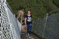 """Switzerland. Canton Ticino. Sementina valley. """"Caracs"""" Tibetan bridge. A teenage girtl with a blue t-shirt """"I love"""" and blue jeans. YouThe 270 m long Tibetan bridge build by the Foundation Curzútt-S. Barnard allows the passage of the rugged valley that separates the communities of Sementina and Monte Carasso, two towns located in front of Bellinzona. The bridge joins the stone made village of Curzútt to the hiking path of """"Via delle Vigne"""", allowing people to make excursions in an area characterized by a landscape rich in cultural heritages. Anchored at a height of 696 m, the bridge rises 130 m above the ground. The walkway, large approximatively one meter, is made of larch wood. Crossing it is a unique experience that represents a true challenge. The safety measures guarantees a risk-free approach and make it a top-attractions either for young intrepid or adventurous families. 14.05.2015 © 2015 Didier Ruef"""