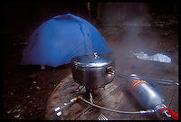 A STAINLESS STEEL COOKPOT SIMMERS ON A ONE-BURNER STOVE AS A TENT IS SEEN IN THE BACKGROUND ON ISLE ROYALE NATIONAL PARK.