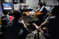 Rural migrants working in a garment sweatshop rest in the evening at their factory accommodation on the outskirts of the southwestern Chinese megapolis of Chongqing. They often work through the nights, earning 1,000 - 6,000 yuan per month depending on work load, a decent income compared with subsistence farming. For many, this is a long and arduous step in the transition from farming to urban living. China is hoping by relocating farmers into cities they would start to buy food, making a break from the cycle of farmers consuming only what they produce. The Chinese government plans to move 250 million rural residents into urban areas over the coming dozen years though it is unclear whether people want to move and where the money for this project will come from. Further urbanisation is meant to drive up consumption to counterbalance an export orientated economy and end subsistence farming but the drive to get people off the land is causing tens of thousands of protests each year. /Felix Features