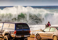 A spectator takes a photograph of a giant wave during a large winter swell at Shark's Cove, North Shore, O'ahu.