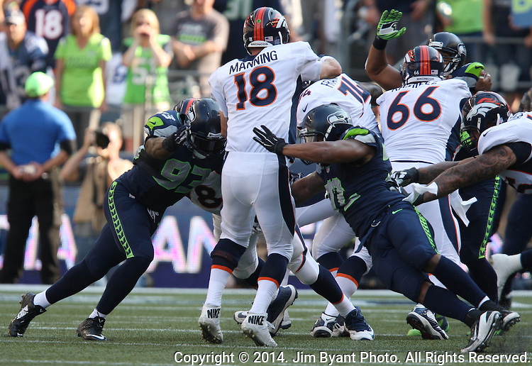 Seattle Seahawks defensive tackle O'Brien Schofield (93) and defensive end Michael Bennett (72) pressure Denver Broncos quarterback Peyton Manning in the fourth quarter at CenturyLink Field in Seattle, Washington on September 21, 2014. The Seahawks won 26-20 in overtime.    ©2014. Jim Bryant Photo. All rights Reserved.