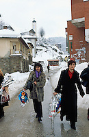 Bosnia and Herzegowina. Republika Serpska. Srebrenica. View on the town and the orthodox church during the winter season. A group of serb women walk on the concrete road and hold in their hands flowers which they have received for Woman's day (march 8). © 2005 Didier Ruef