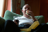 Obese man eats burger with cola drink. UK  (r