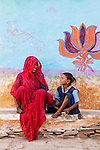 Mother and daughter near a colorful wall mural, Rajasthan, India