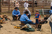 Saddle Bronc rider, Jake Costello, behind chutes with son who came dressed as Superman, Miles City Bucking Horse Sale, Montana