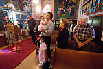 Liturgy service at St. Sava Orthodox Church, Jackson, Calif...Families during prayer about to accept the sacrament of the Body of Christ at the end of the worship service.