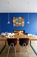 In the dining area of the open-plan living space the massive concrete wall has been painted bright blue and the fireplace goes through to the living area on the other side