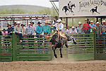 A saddle bronc rider in the air as the cowboys watch at the Jordan Valley Big Loop Rodeo, Ore.
